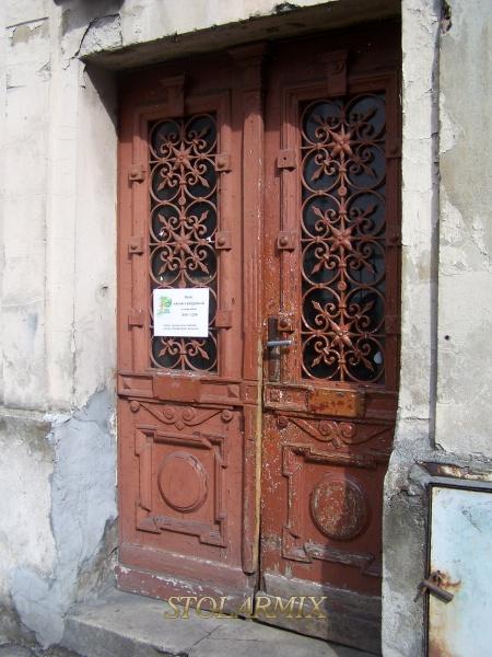 Stare drzwi z kratami ozdobnymi, które posiadają wszystkie połączenia nitowe. Drzwi przed renowacją. Na drzwiach widoczne zniszczenia, które spowodowała długoletnia eksploatacja. Ząb czasu nieubłaganie wywarł na nich swoje piętno.