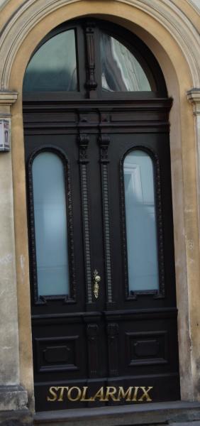Drzwi do zabytkowej kamienicy po renowacji z odtworzeniem nie istniejącej snycerki.