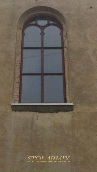 Przykład okna zabytkowego z pięknymi łukami i wykończeniem zewnętrznym w formie wałków. Całość szprosów okna jako konstrukcyjne.