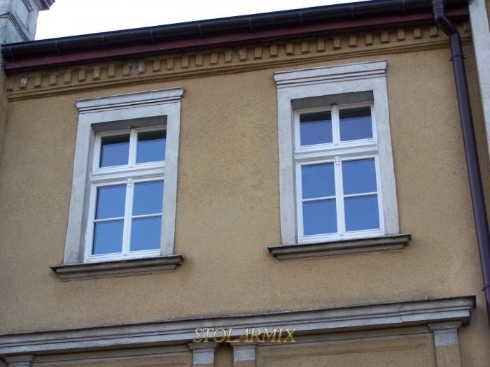 Okna stylizowane na wzór istniejących w zabytkowym budynku, lecz w formie współczesnej z szybami zespolonymi.
