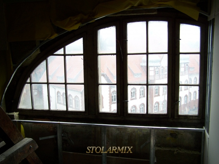 Okna zabytkowe skrzynkowe z szprosami w kształcie łuku.